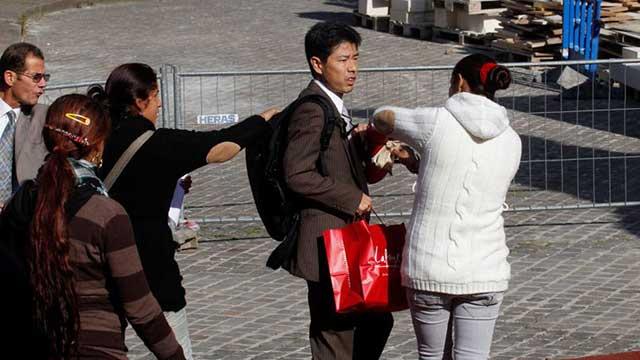 ロマの女たちに買ったばかりの紙袋を強奪されるアジア人